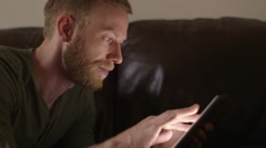 Young man using touchscreen tablet technology and reading. Stock Footage