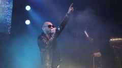 Cool lead singer of music group in sunglasses sings and jumps - stock footage