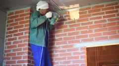 Worker in workwear makes hole in wall with large perforator Stock Footage