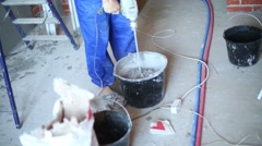 Legs of worker with hand mixer preparing mix for plaster wall Stock Footage