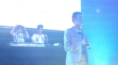 Young man sings and two djs works on stage in nightclub Stock Footage