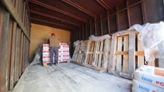 Man unload truck with sacks of dry mortar Knauf. Stock Footage