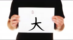 Man holding white message board with Chinese character for big calligraphy Stock Footage