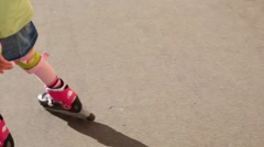 Legs of girl in protection of knees riding roller skates Stock Footage