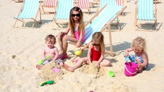Four children  play by shovels and buckets sitting on sand. Stock Footage