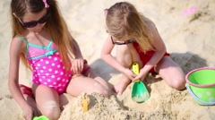 Two happy little girls sit on beach and play with sand Stock Footage