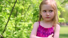 Sullen little girl stands with her arms crossed on the chest - stock footage