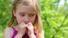 Sullen little girl stands crumpling her lips with fingers - stock footage