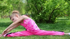 Little girl sits on grass, leaning to one foot and another. - stock footage