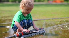 Little boy plays with sprinkler in puddle, then water ends. Stock Footage