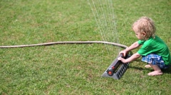 Little curly boy plays with sprinkler and looks at jets in garden Stock Footage