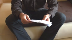 Headless shot man opening envelope with bill inside, reading the letter home - stock footage