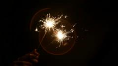 lit sparkler in hand on a dark background - stock footage