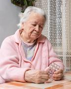 old sad woman holding pills - stock photo