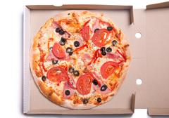Tasty pizza with ham and tomatoes in box Stock Photos