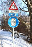 Street sign and an indication of the road slippery and snow chains Stock Photos