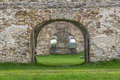 fragment of stone old ruins overgrown with grass - stock photo