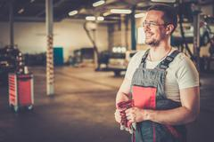 Serviceman in a car workshop Stock Photos