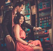 Beautiful couple near slot machine in a casino Stock Photos