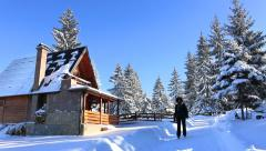 Woman on winter vacation, Woman walks around mountain house Stock Footage