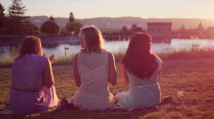 Three young women spending time together in the park at sunset - stock footage