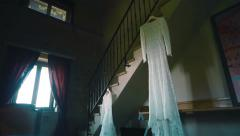 Lace wedding dress hanging on ladder in antique room. Pan Stock Footage