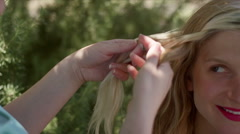 Young blonde woman gets her hair braided Stock Footage