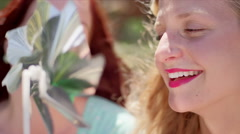 Close up of women blowing on pinwheel Stock Footage