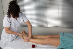 foot massage. female hands giving massage to soft bare foot - stock photo