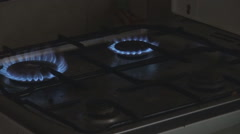 Ignite all four burners of kitchen stove, gas cooker stove, dark background room Stock Footage