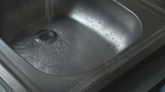 Hand turn on the sink water flowing, home flood danger water drain, kitchen tool Stock Footage