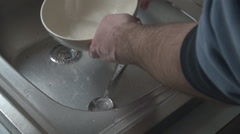 Closeup kitchen sink, man washing dishes, milk bowl and metal spoon get cleaned Stock Footage
