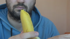Closeup white young man with beard peel ripe banana, eat fresh fruit, chewing Stock Footage