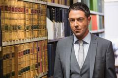 Lawyer looking at camera in the law library - stock photo