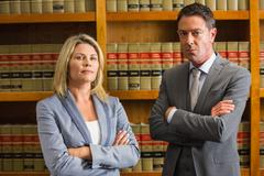 Lawyers looking at camera in the law library - stock photo