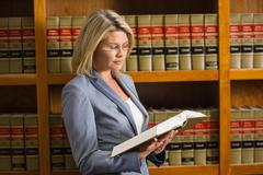 Lawyer reading book in the law library - stock photo