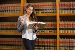 Stock Photo of Pretty lawyer reading in the law library