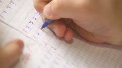 First steps in writing: little pupil write digits in square grid notebook Stock Footage