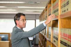 Lawyer picking book in the law library - stock photo