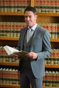 Lawyer holding book in the law library - stock photo