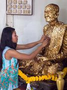 Girl sticks a slice of golden on buddha statue Stock Photos