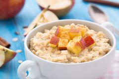 Tasty oatmeal with apples and cinnamon - stock photo