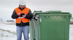 Inspector with cell tablet PC near the garbage containers Stock Footage