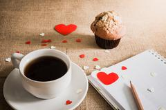 chocolate muffin and coffee and hearts on sackcloth textures - stock photo