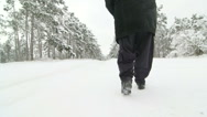 Stock Video Footage of Elderly woman walking on snowy road through a forest in winter