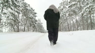 Stock Video Footage of Lonely senior woman walking along the road through the winter woods in snow