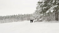 Stock Video Footage of Man with an older woman walking down the a snowy road through a winter forest
