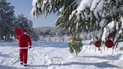 Santa Claus with a bag of gifts coming in the winter woods Stock Footage