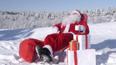Santa Claus relaxing in lounge chair at winter ski resort Stock Footage