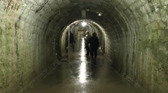 Visitors in a typical damp corridor inside Fort Douaumont, near Verdun, France. Stock Footage
